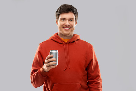 drinks and people concept - happy young man in red hoodie drinking soda from tin can over grey background