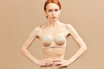 Skinny suffering female in nude underwear tied her waist with measuring tape posing over anorexia and eating disorders