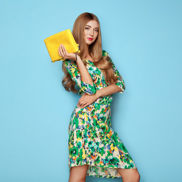 Blonde Young Woman in Floral Spring Summer Dress. Girl Posing on a Blue Background. Summer Floral Outfit. Stylish Wavy Hairstyle. Fashion Photo. Glamour Lady with Yellow Handbag