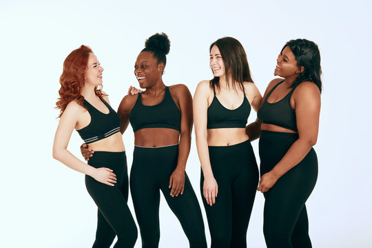 Group of four women of different race, figure type and size in sports outfit talking lively and laughing over white background.