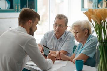 Businessman talks with elderly parents