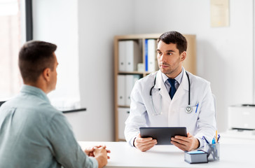 medicine, healthcare and technology concept - doctor with tablet pc computer and male patient talking at medical office in hospital