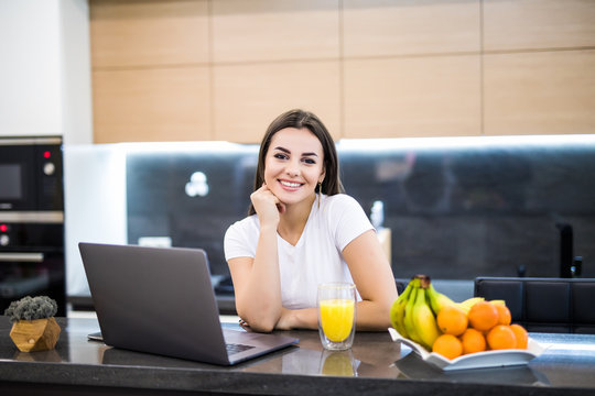 Portrait of a young smiling woman sitting in front of her laptop in the kitchen