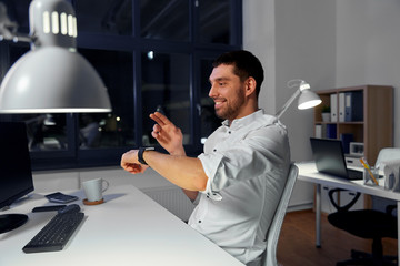 business, technology and ai concept - smiling businessman using gestures with smartwatch at nigh office