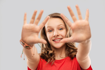 people concept - smiling teenage girl with long hair in red t-shirt giving high five over grey background