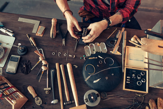 guy is sitting at messy desk in the workshop, top view cropped photo