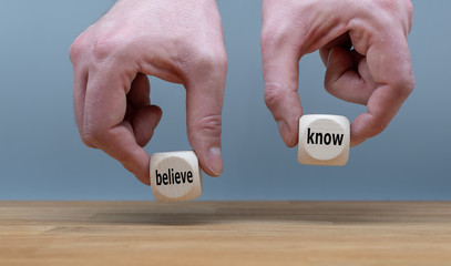 """Conflict of knowing or believing. Two Hands hold two dice with the words """"believe"""" and """"know"""". The dice with the label """"know"""" is chosen."""