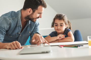 Father teach his daughter to draw.They sitting in living room.Education and family concept.
