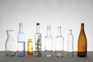 Verschiedene Glasflaschen vor weißem Hintergrund auf Tischdecke aus Leinen, im Gegenlicht