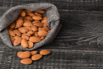 Almonds in gray bag on textured  dark wooden background, top view. Copy space.