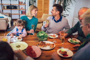 Multi generation family enjoying meal around table at home