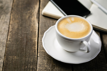 BUsiness morning concept - coffee, notebook, phone, rustic wood background