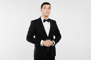 Fashionable and handsome young emotional man in white shirt and in the stylish black suit with bow tie, isolated at white background