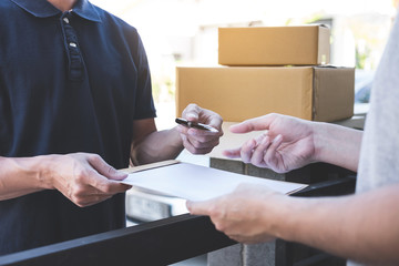 Delivery mail man giving parcel box to recipient, Young man signing receipt of delivery package from post shipment courier at home