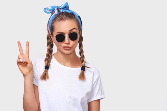 Studio portrait of cheerful blonde young woman wearing trendy sunglasses, white t-shirt and blue headband, making a duck face and showing peace sign. Student girl going crazy with braids hairstyle