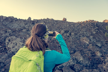 Female hiker taking phots of spectacular volcanic landscape.