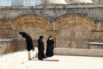 Palestinian Muslim women stand on a plaza next to the Golden Gate near Al-Aqsa mosque in Jerusalem's Old City