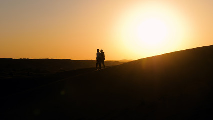 Male silhouettes in desert