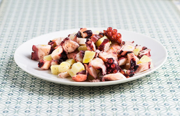 Portion of octopus salad and potatoes on vintage background