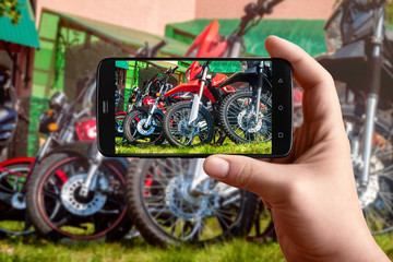 Men hands taking pictures of motorbike phone. Group of motorcycles, bikes. Photos of the smartphone for the post in social networks.