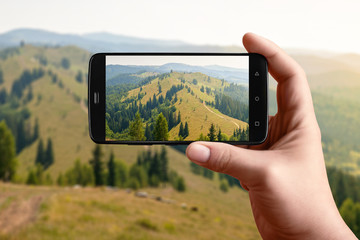 A smartphone in hand photographs the nature of the mountains on the screen. Photos of mountain scenery for posting on social networks.
