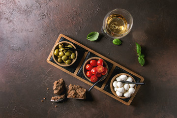 Mozzarella, cherry tomatoes, olives antipasto appetizers served in wooden bowl on slate serving board with glass of white wine, basil and rye bread over brown texture background. Flat lay, space