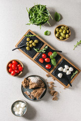 Mozzarella, cherry tomatoes, olives antipasto appetizers served in bowls and on slate serving board with basil, arugula and rye bread over grey texture background. Flat lay, space