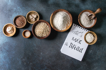Ingredients for baking bread. Variety of wheat and rye flour, grains, yeast, sourdough and notebook with handwritten lettering over dark blue texture background. Flat lay, space