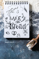 Ingredients for baking bread. Variety of wheat and rye flour, grains, notebook with handwritten lettering over dark blue texture background. Flat lay, space