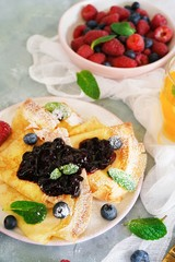 French crepes with blueberry compote topping, selective focus