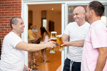 Three Happy male friends relax drinking beer night out home terrace. Friendship concept