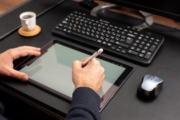 Designer Working On Digital Tablet Using Stylus Pen on Work Desk