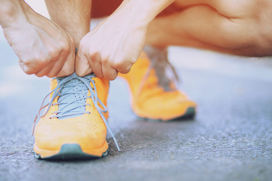 barefoot running shoes close up. male athlete tying laces shoelace for jogging on road concrete floor. Runner ties getting ready for training. Sport lifestyle.