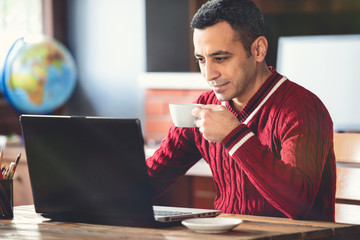 Man Working on Computer and Having His Coffee in Office Room