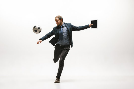Businessman with tablet and football ball in office. Soccer freestyle. Concept of balance and agility in business. Manager perfoming tricks isolated on white studio background.