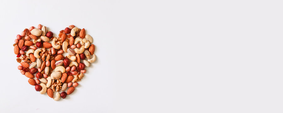 Mixed nuts forming a heart shape isolated on white background. Top view or flat lay