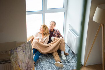 smiling couple with coffee cups sitting on floor by large window at new home