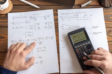 Civil Engineer or University Student Making Calculations Using Scientific Calculator