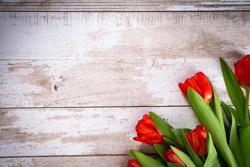 Czerwone tulipany na drewnianym tle