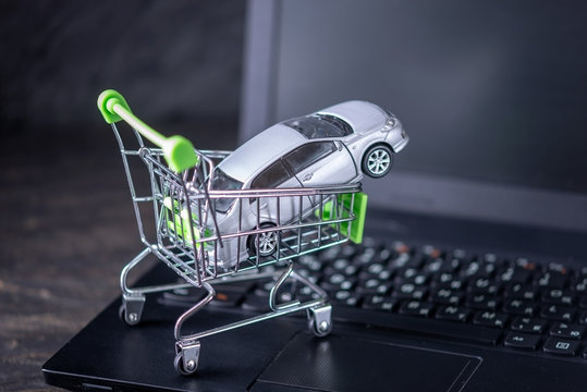 Shopping basket with car on laptop keyboard on dark background. Concept of online shopping vehicles on the Internet