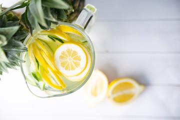 Owocowa lemoniada w szklanym dzbanku. Cytryny i ananas