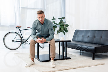 handsome businessman sitting on coffee table and using smartphone while looking at camera