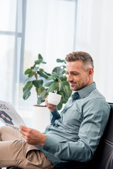 happy businessman sitting on sofa and holding cup while reading newspaper
