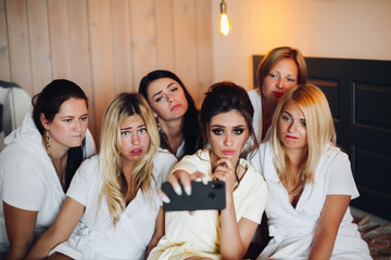 Group of pretty ladies with a bride in the middle in white taking selfie. They are having a hen party in a hotel or relaxing in spa.