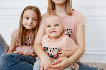Light family series. Three sisters on a white background, dressed in funny t-shirts and jeans