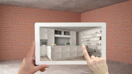 Augmented reality concept. Hand holding tablet with AR application used to simulate furniture and design products in interior construction site, classic kitchen with island