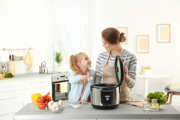 Mother and daughter preparing food with modern multi cooker in kitchen