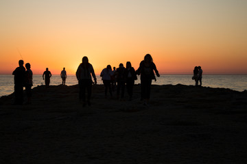 Silhouette of group of people watching the sunset on the sea