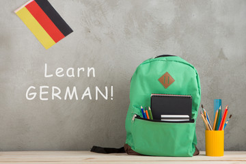 backpack, flag of the Germany, school supplies against a cement wall with text