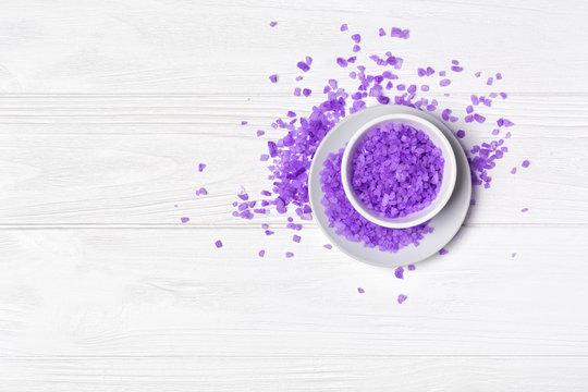 Flavored lavender sea salt crystals for bath on white wooden background
